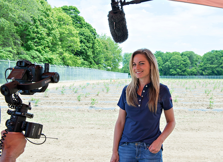 Deborah Sikkema is surrounded by camera equipment in front of a cannabis field