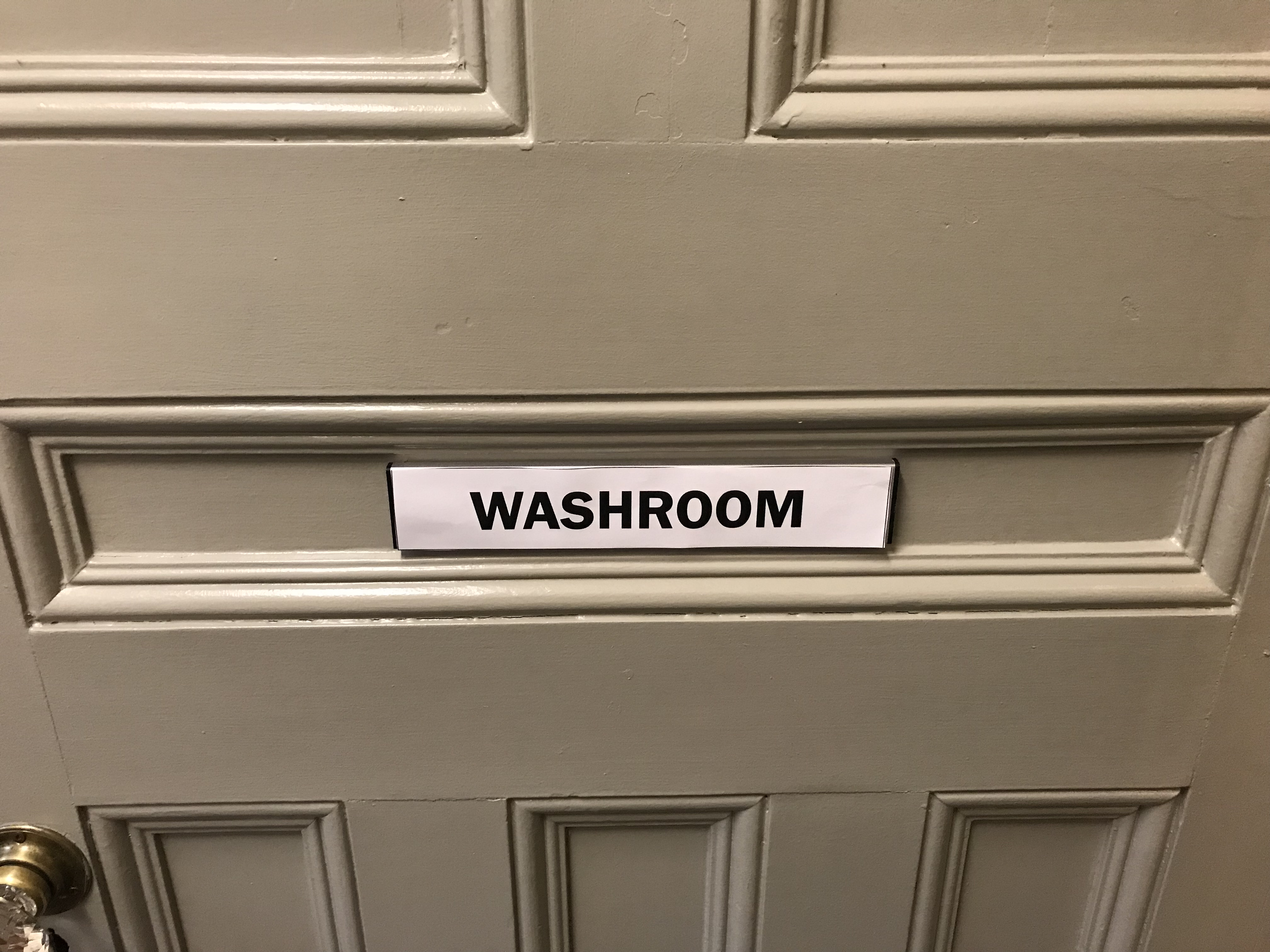 """Photo of a door with a paper sign reading """"washroom"""""""