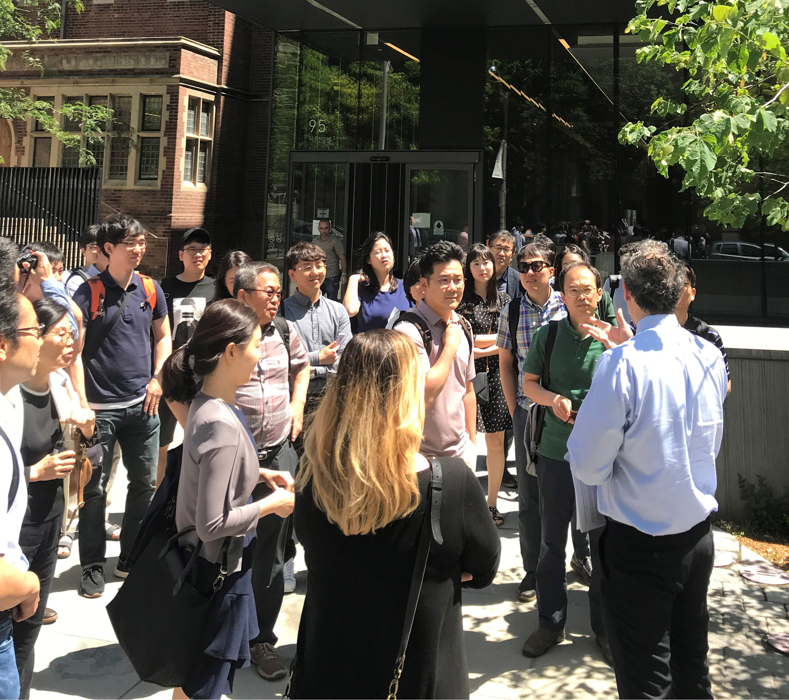 Rafael Gomez speaks to a group in front of the Rotman building