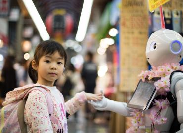 Photo of a child holding hands with a robot