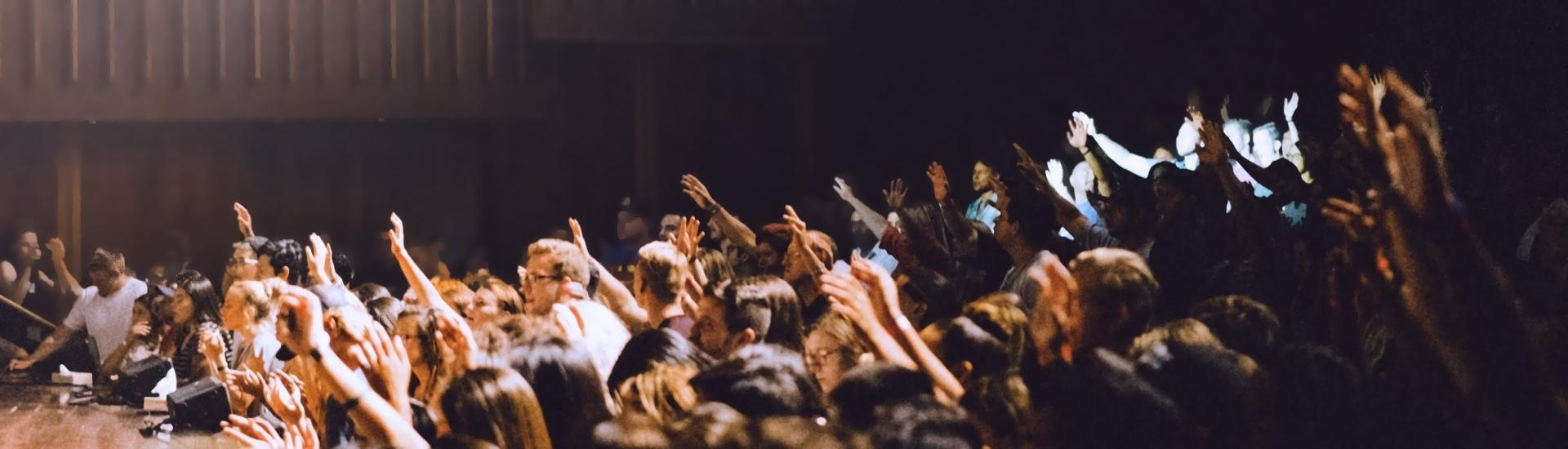 Photo of a crowd with hands raised