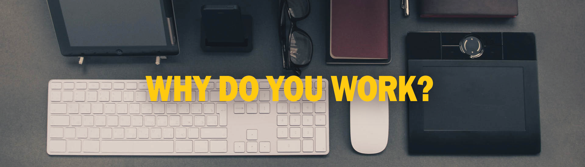 Why do you work? in yellow text over a photo of a computer workstation